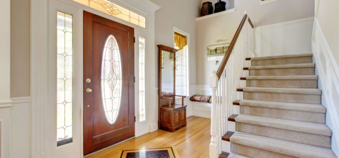 Home Entry Way With Wood Floor and Carpeted Stairs
